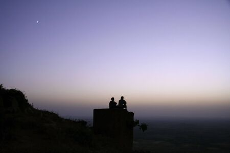 chilling out: couple chilling out on top of hill