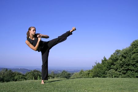 self defence: lateral kick - attractive young woman practising self defense