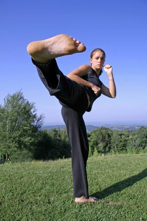 self defense: sole kick- attractive young woman practising self defense Stock Photo