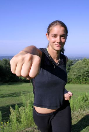 girl punch: friendly punch - attractive young woman practising self defense