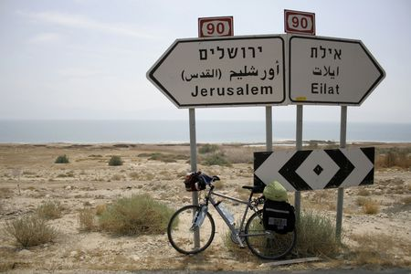 eilat: bicycle parked against the jerusalem and eilat road signs Stock Photo
