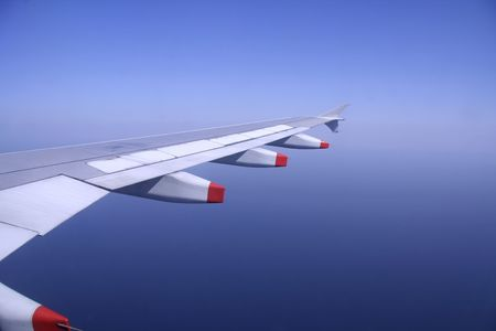 long haul journey: aeroplane wing flying in the sky Stock Photo