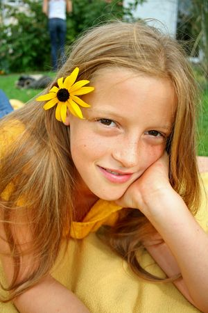 preteen model: young girl posing with flower in her hair and chin in hand Stock Photo