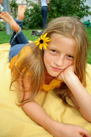 young girl on blanket posing with flower in her hair