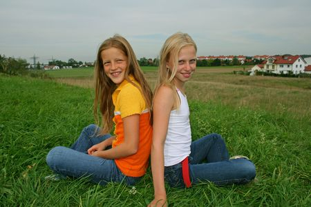 two young girl friends sitting in cross-legged pose in field Stock Photo - 4556682