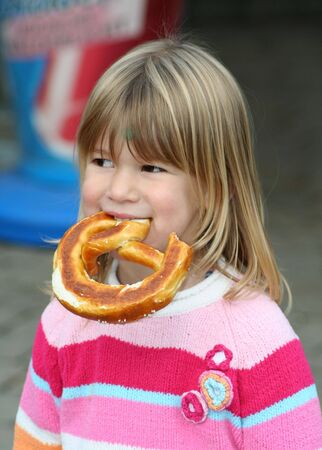 without people: little girl eating a piece of bread with her hands
