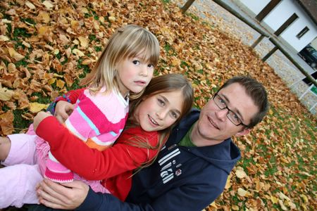 father with his two daughters sitting in a park in autum leaves photo