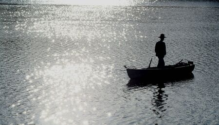 silhouette of fisherman on boat on lake Stock Photo - 4435846