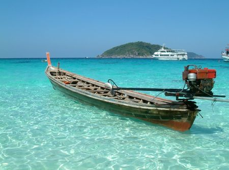 insular: longtail motor boat moored in blue tropical waters, similan island, thailand