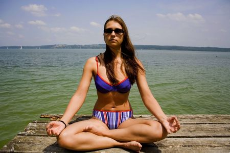 close up of woman meditating on lake pier Stock Photo - 3936953
