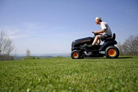 man sitting on a lawnmower photo
