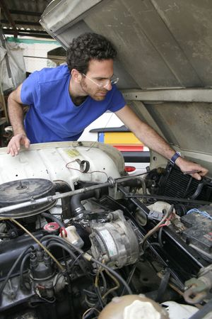 engine bonnet: young man doing mechanical work on car engine