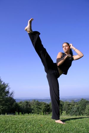 self defense: split kick - attractive young woman practising self defense