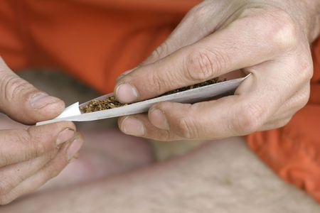 hippie preparing, rolling and smoking marijuana joint : photos series