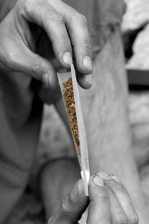 inhaling: hippy preparing, rolling and smoking marijuana joint : photos series