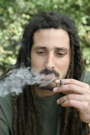 hippy preparing, rolling and smoking marijuana joint : photos series photo