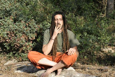 hippie preparing, rolling and smoking marijuana joint : photos series