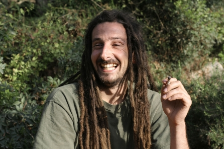 dreadlock: hippy preparing, rolling and smoking marijuana joint : photos series