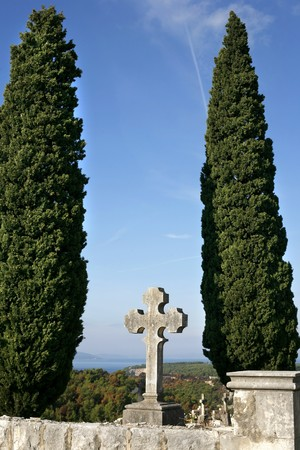 crucifiction: tombstone crosses on blue mediterranean sky with cypruses