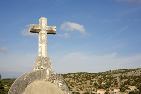 crucifiction: white stone cross on blue sky and cloudy background Stock Photo