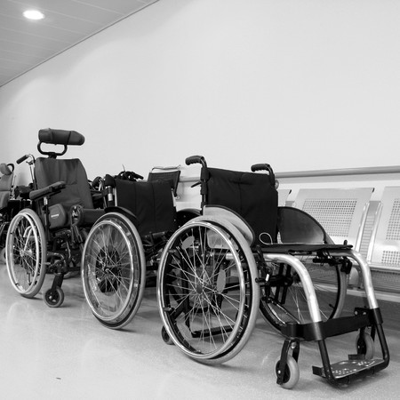 aide: monochromatic photo of wheel chairs parked in a hospital corridor