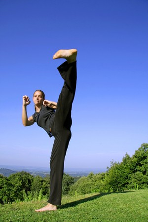 in your face kick - attractive young woman practising self defense Stock Photo