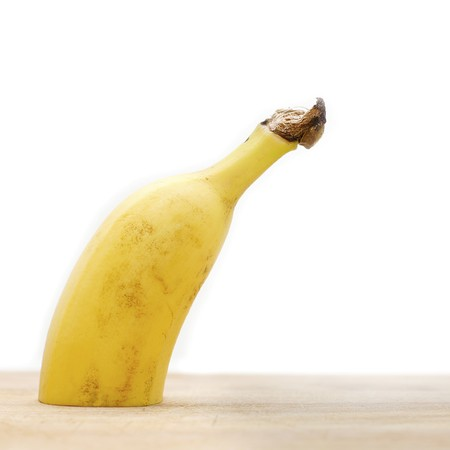erection: Half banana standing on cutting board leaning right