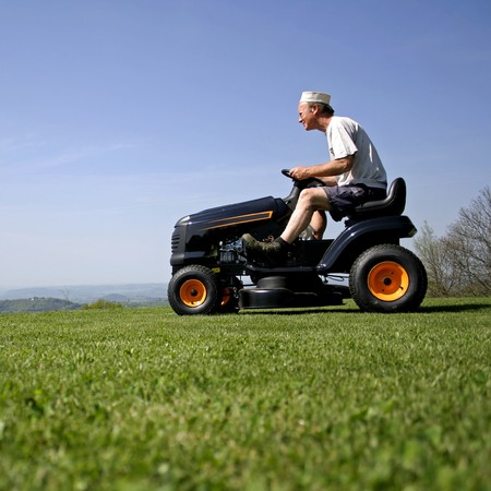 man sitting on a lawnmower in his garden Stock Photo