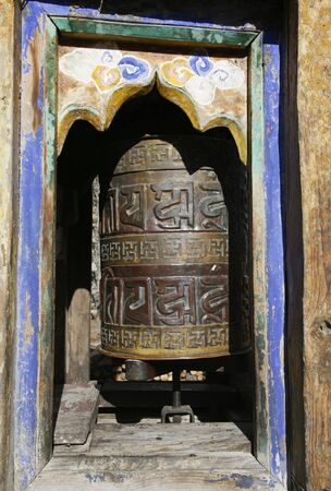 Traditional praying wheels at the entrance and exit of Nepali villagers on the Annapurna trail photo