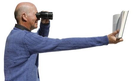 Short sighted man needs binoculars to read his book Stock Photo