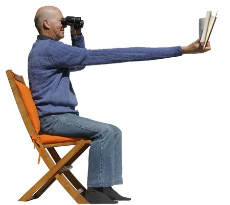 Short sighted man needs binoculars to read his book Stock Photo