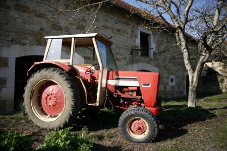 Old red tractor in front of farm in Correze, France photo