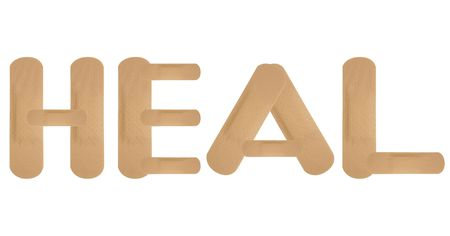 Plaster band aids spelling HEAL on white background photo