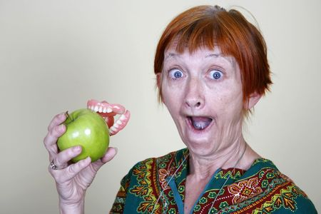 Elderly lady losing her teeth on a bite of an apple