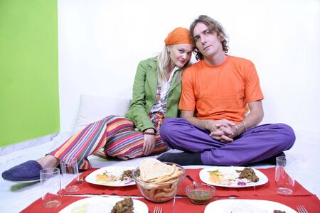 Young couple in their 20s eating on the floor in their living room photo