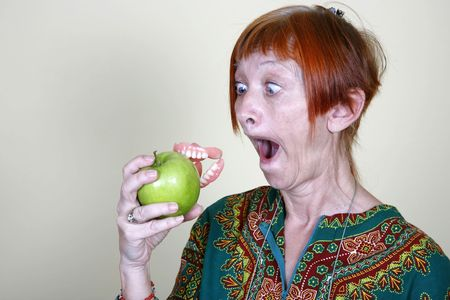 granny smith: Woman losing her false teeth by biting into an apple