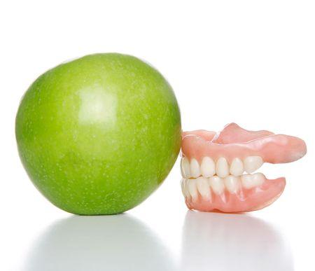 granny smith apple: False teeth denture against green granny smith apple