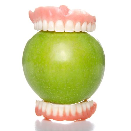 False teeth having a big bite into a green apple Stock Photo