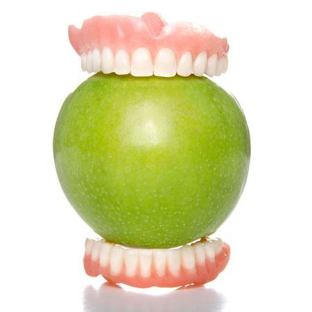 unecht: Zahnersatz mit einem gro�en Biss in einen Apfel gr�n Lizenzfreie Bilder
