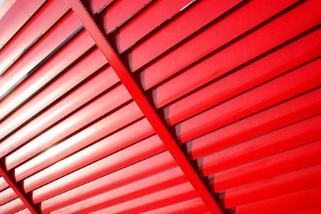 jalousie: Diagonal red metal venetian blind separation wall on building rooftop Stock Photo