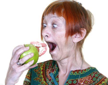 unecht: Frauen verlieren ihre falschen Z�hne, die durch Bei�en in einen Apfel