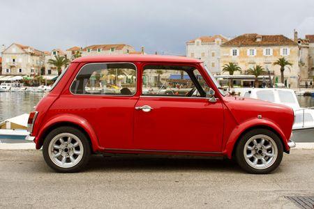 parked: Rode mini auto geparkeerd in het dorp in de Middellandse Zee
