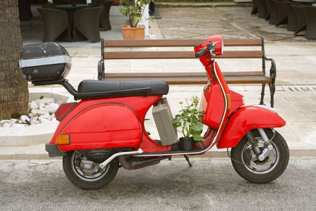 old red vespa with plant parked in village in the mediterranean photo