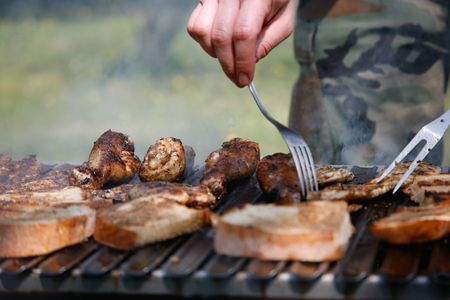 Man preparing grilled meat on a barbecue in summer in the garden photo