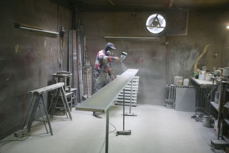Man painting with spray paint gun in his home workshop photo