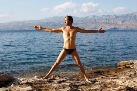 Young man doing yoga on beach on the island of Brac, Croatia Stock Photo - 5901480