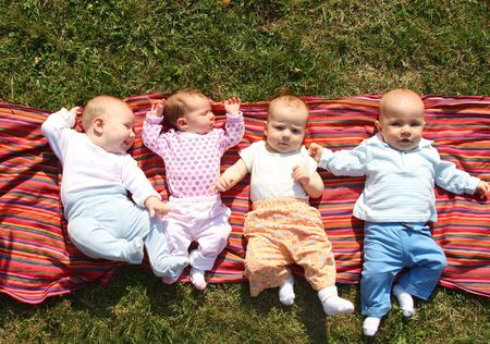 Four babies lying on colourful cloth in grass in park Stock Photo