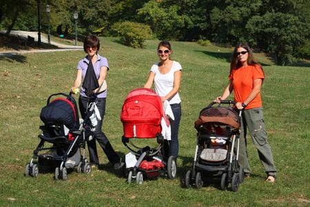 Mothers pushing their prams through the park in summer photo