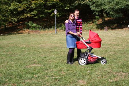 Young couple with pram in park on a sunner autumn day photo
