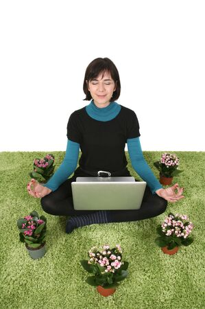 woman sitting on grass with flowers around her meditating with a laptop photo